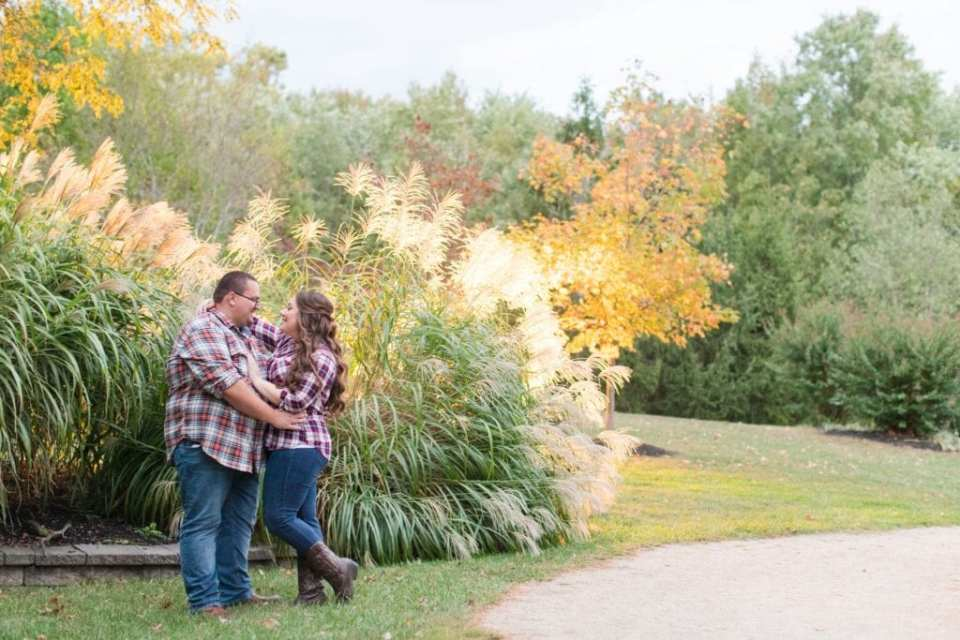 Wide angle photo of the engaged couple in their flannel shirts and jeans, within one another's arms, during their Sayen Gardens engagement photos