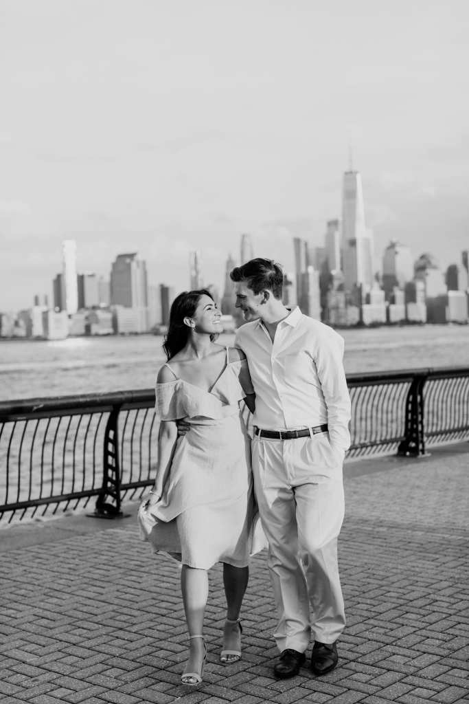 Black and white of the couple with their arms wrapped around one anothers waists, facing the camera, on the Hoboken waterfront, New York City skyline in the background