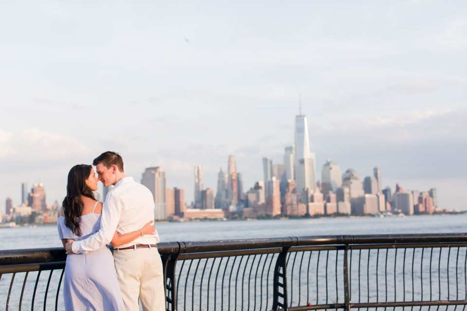 Engaged couple on the Hoboken waterfront, bodies facing the New York City skyline, their arms wrapped around one anothers waists, looking at one another, nose to nose. the Freedom Tower in the distance behind them
