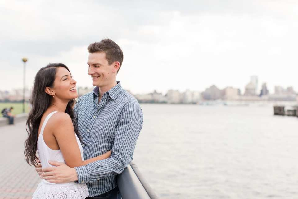 Couple in one anothers arms, casually leaning up against a railing on the waterfront in Hoboken, New Jersey. Her top by J. Crew, his shirt from Nautica