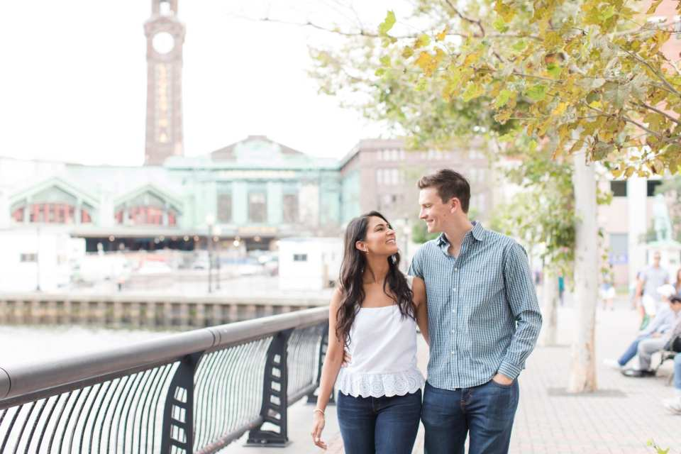 Couple smiling at each other while walking along the waterfront in Hoboken, New Jersey, the Hoboken train station in the distance