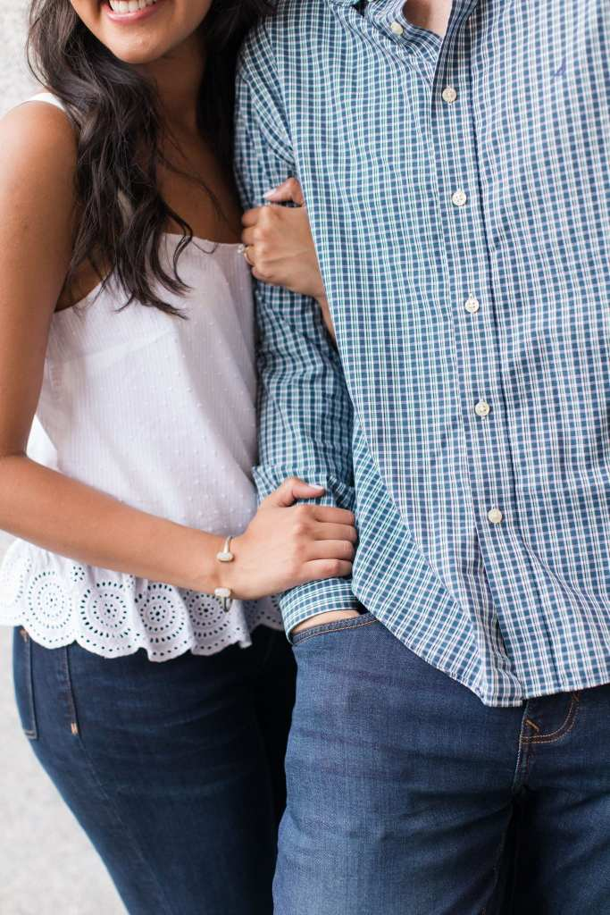 Close up of the couple, she has her arms wrapped around his right arm. She is in a top from J.Crew, his shirt by Nautica