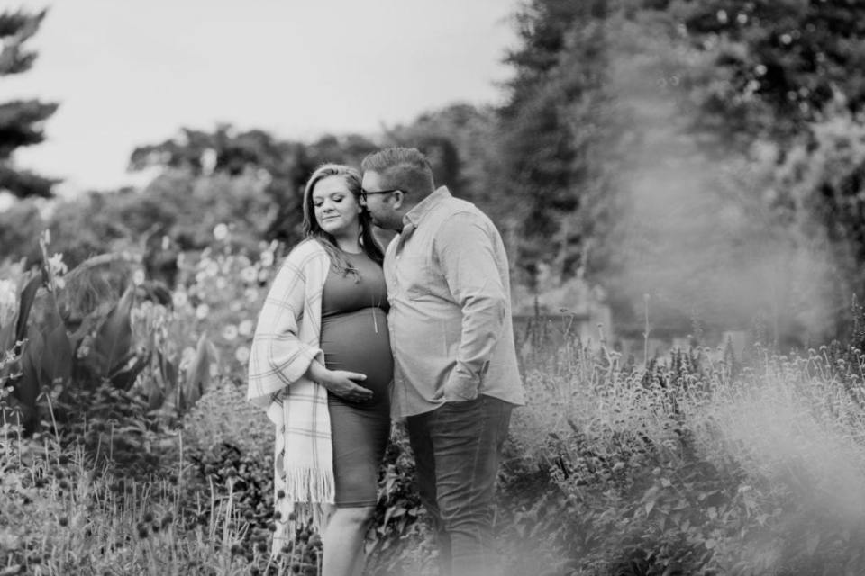 Black and white photo of Dad to be nuzzling Mom to be as she holds her pregnant belly amongst the foliage at Rutgers Gardens