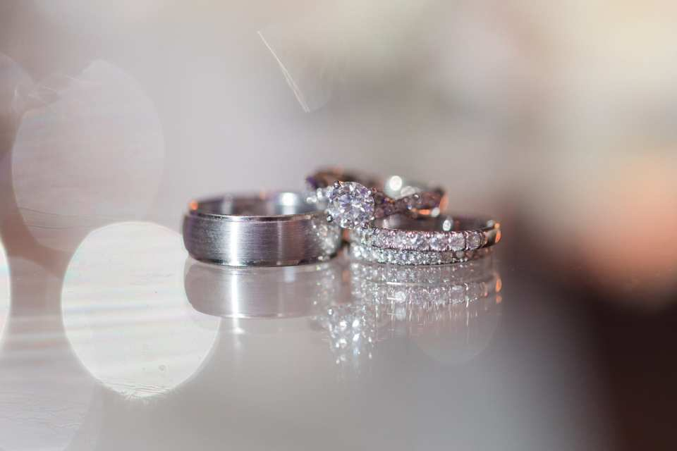 Wedding detail shot of the bride and grooms wedding bands along with the brides round diamond engagement ring