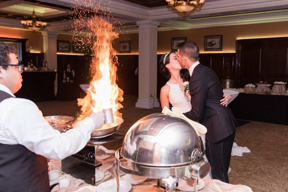 Groom slightly dipping the bride while kissing her while a chef flambe's on the left side of the photo inside the Palace at Somerset Park