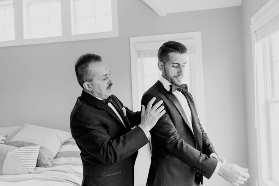The groom being helped into his custom Enzo tuxedo by his father