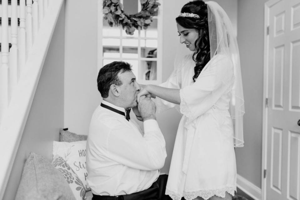 The bride in her getting ready short white robe, her hands being kissed by her father