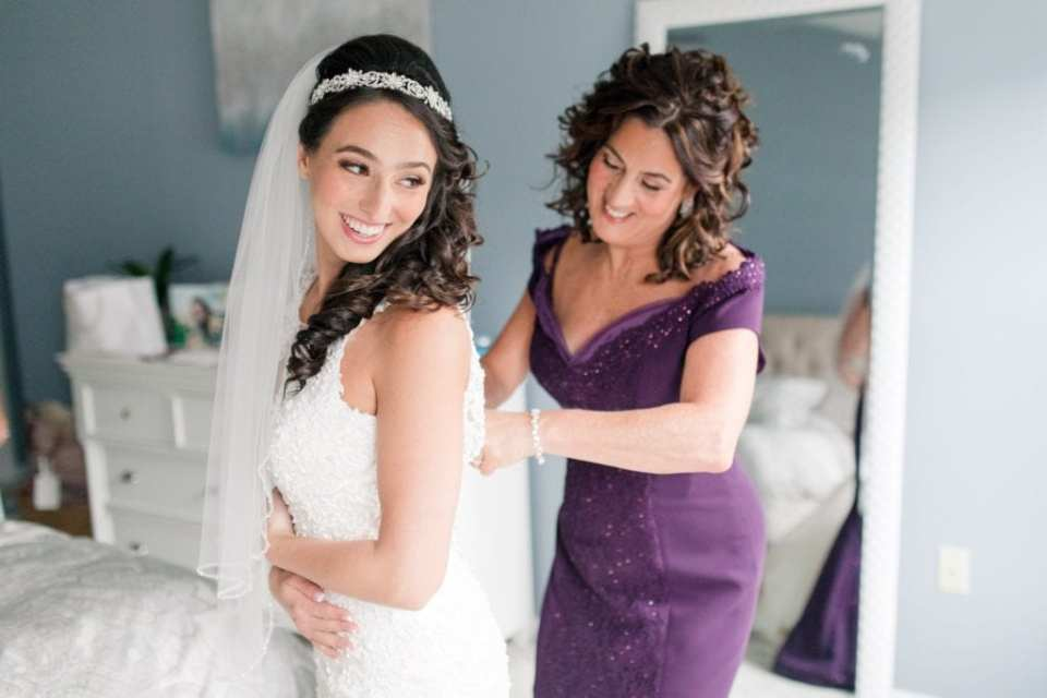 The bride being helped into her Maggie Sottero gown by her mother
