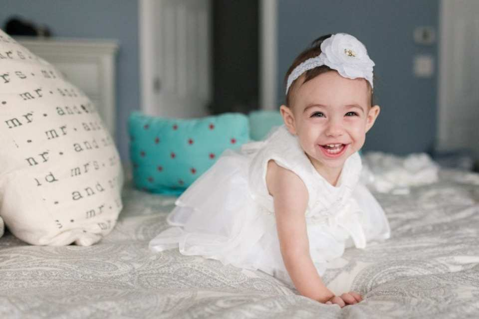 """The flower girl smiling at the camera while on a bed next to a pillow that says """"mr and mrs"""""""