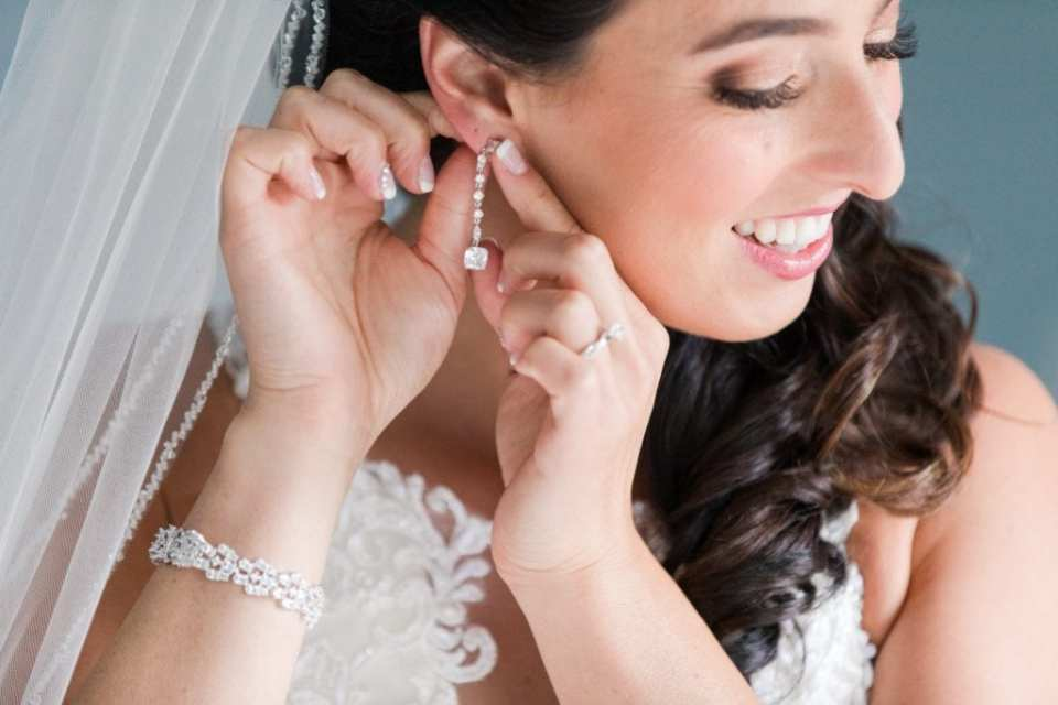 Close up of the brides face as she puts in her dangling rhinestone earring