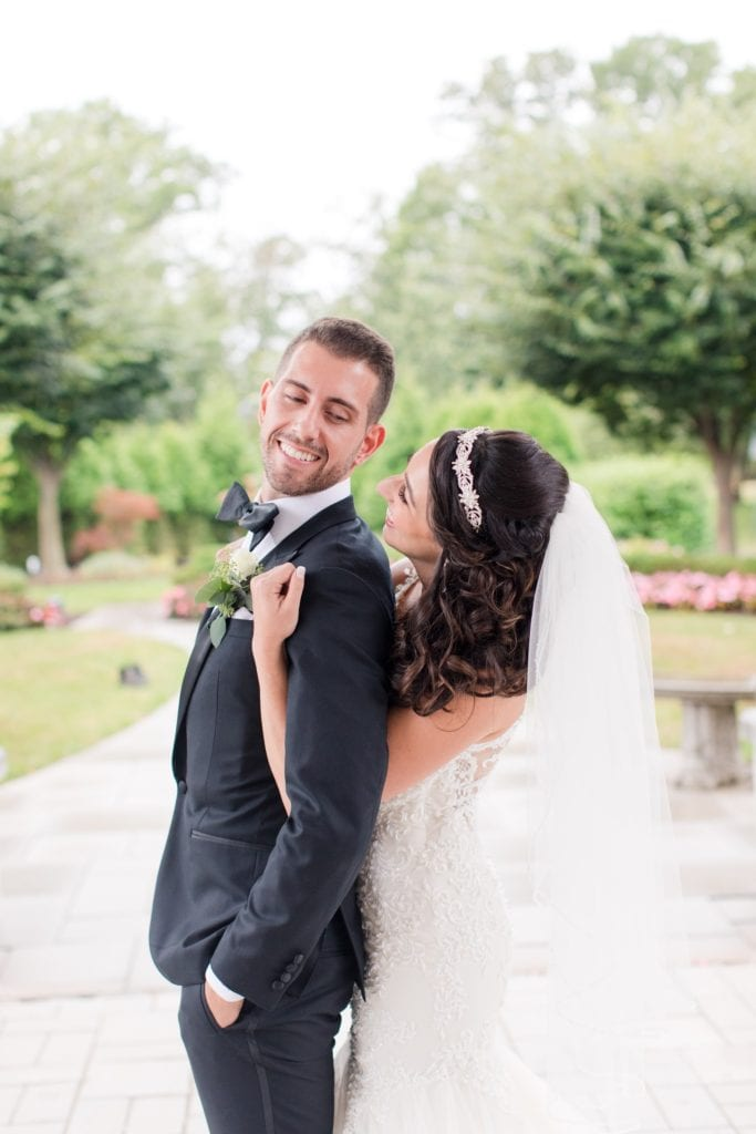 Side view of bride and groom; she is behind him, arms under his arms, his hands in his pockets. He is looking over his left shoulder looking back at her as she looks up at him