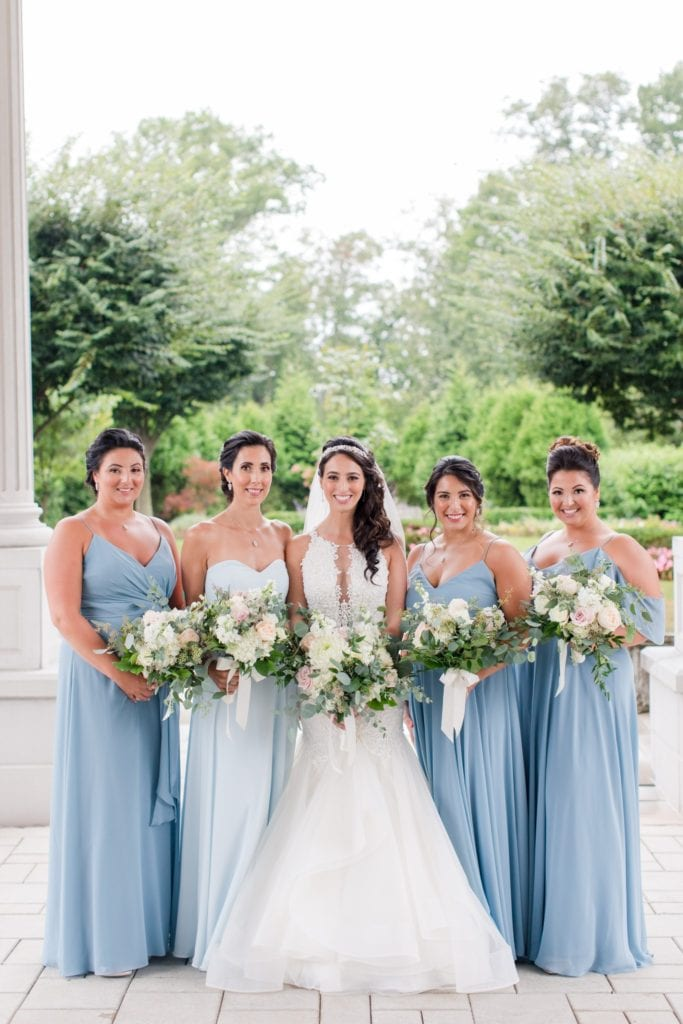 Formal bridal party photo with the bride. Bridal party dresses in various shades of blue by Jenny Yoo, bridal gown by Maggie Sottero on the grounds of the Palace at Somerset Park