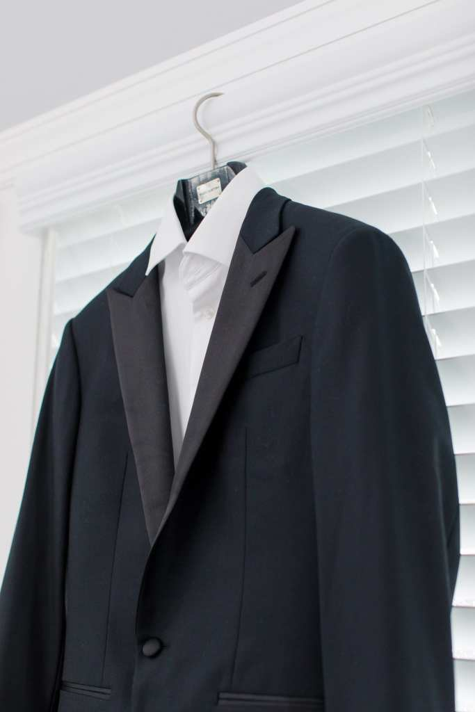 Grooms custom Enzo tuxedo hanging on hanger on white windown frame
