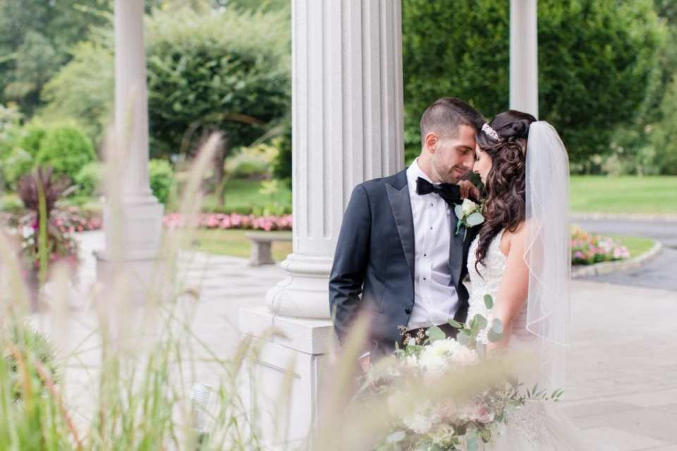 Intimate portrait of bride and groom outside of the Palace at Somerset Park facing each other, foreheads together.