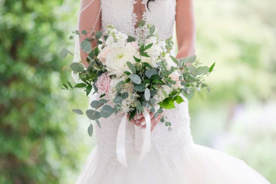 3/4 body shot of the bride holding her bridal bouquet of a variety of white and blush florals with a variety of greens by Jacquelines Florist, bouquet at waist in focus