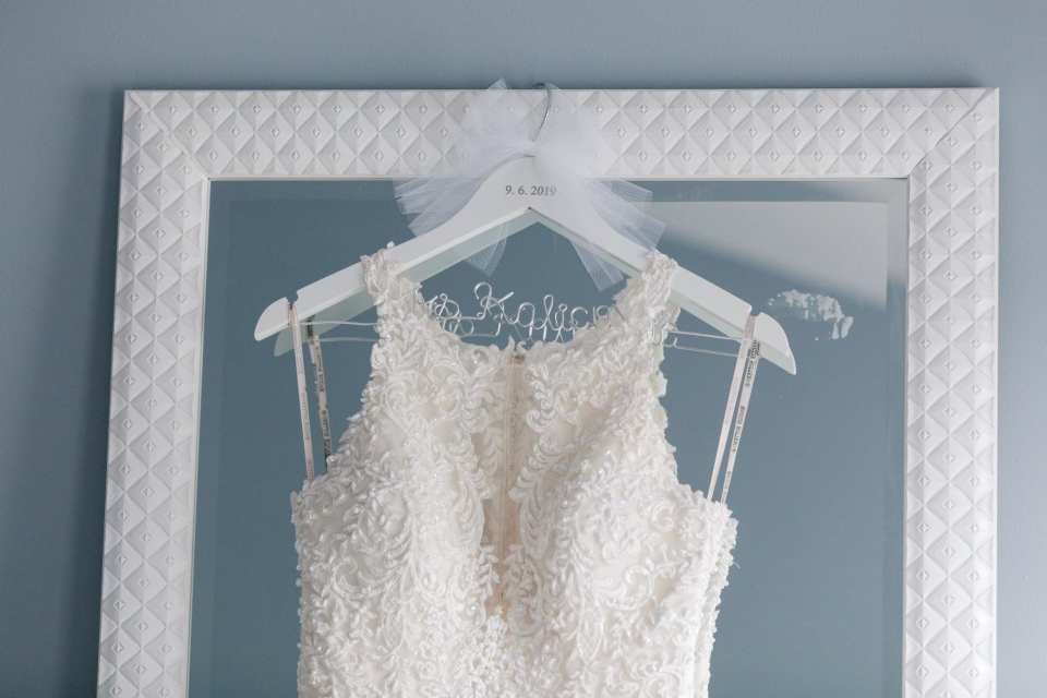 Bridal gown hanging on custom white hanger with brides married name and date of wedding