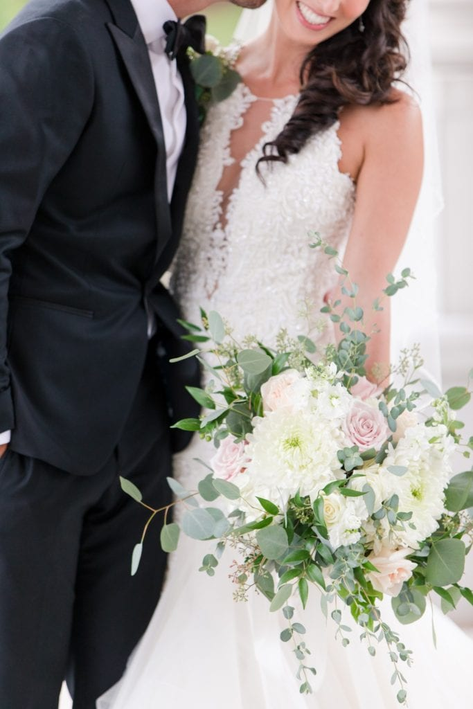 3/4 boy shot of the bride and groom, he is slightly dipping her, her bridal bouquet by Jacquelines Florist of a variety of white and blush florals with greens in focus
