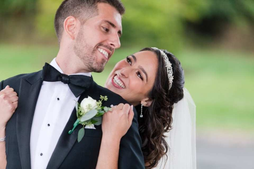 Candid photo of bride and groom having fun with one another, she behind him, arms under his, he looking back at her