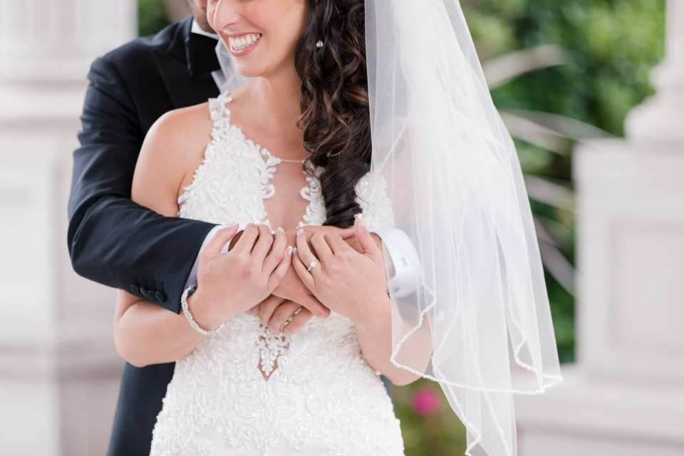 Half body shot of bride and groom, his arms wrapped around her body, her arms wrapped under his, her engagement ring in focus