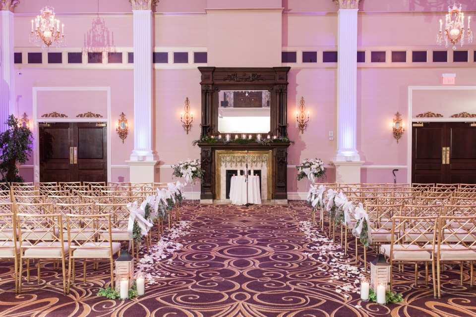 Wide angle photo of the ceremony room with gold chivari chairs and ornate dark wood doors and fireplace with mirrored mantle at the Palace at Somerset Park