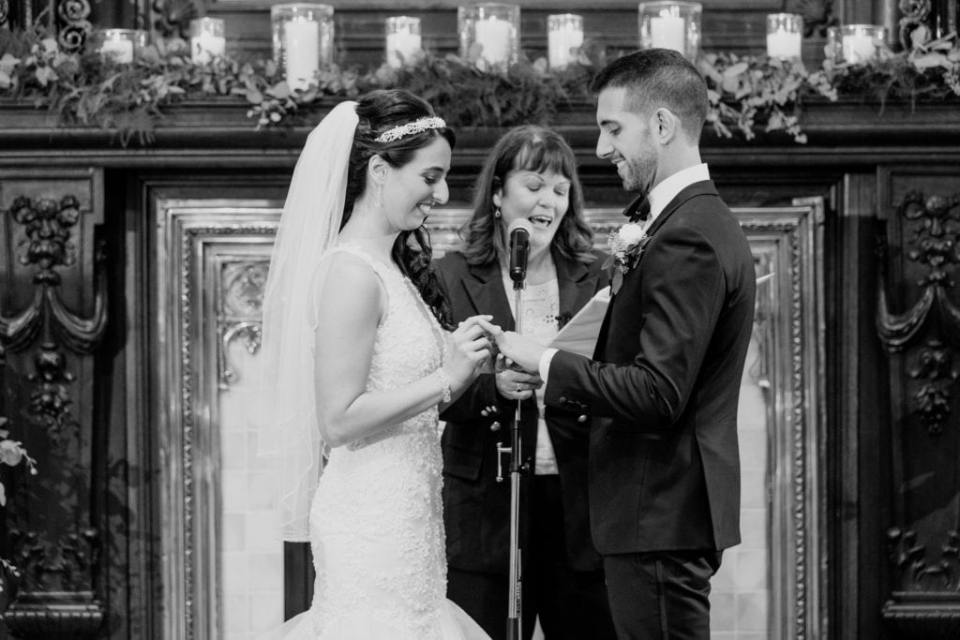 Black and white close up of the bride and groom exchanging rings during their wedding ceremony
