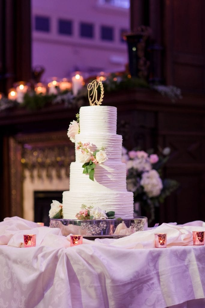 Gold monogram K atop the four tier white wedding cake decorated with a simple lined texture and rose florals by the Palace at Somerset Park weddings