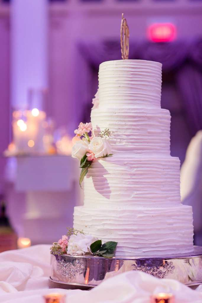Four tier white wedding cake decorated with a simple lined texture and rose florals by the Palace at Somerset Park weddings