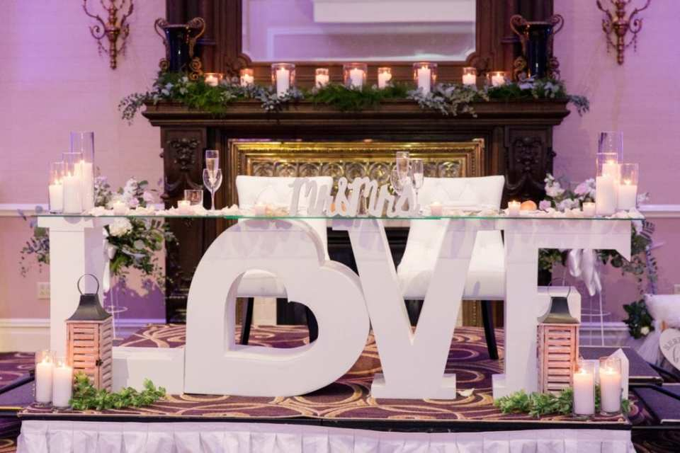 """Sweet heart table which is a wooden white table in the shape of the word LOVE the """"O"""" in the shape of a heart, surrounded by candles at the Palace at Somerset Park"""