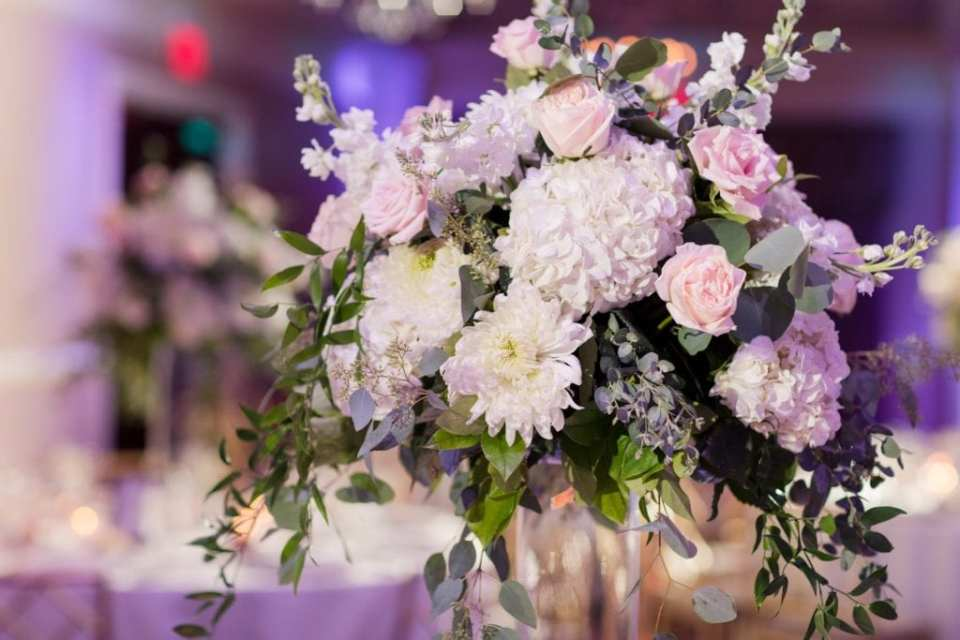 Close up of a tall floral arrangement of white and blush florals and greens on top of a clear cylinder vase by Jacquelines Florist at a Palace at Somerset Park wedding