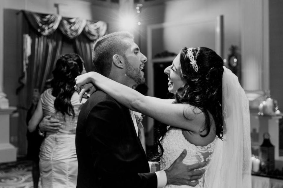Black and white candid photo of the bride and groom laughing while dancing
