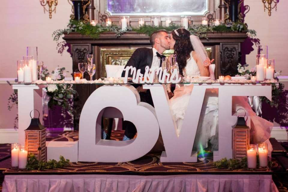 """Bride and groom kissing at their sweet heart table which is a wooden white table in the shape of the word LOVE the """"O"""" in the shape of a heart, surrounded by candles at the Palace at Somerset Park"""