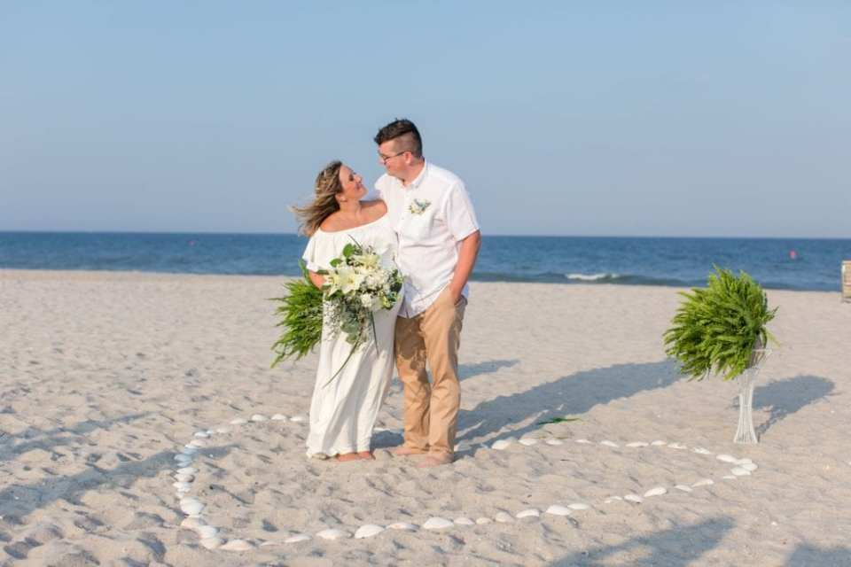 The bride in her off the shoulder white gown looks up at her groom in a white button down short sleeve shirt and khakis, while holding her bouquet, arms wrapped around one anothers back, inside a heart formed from shells after their Lavallette Beach elopement