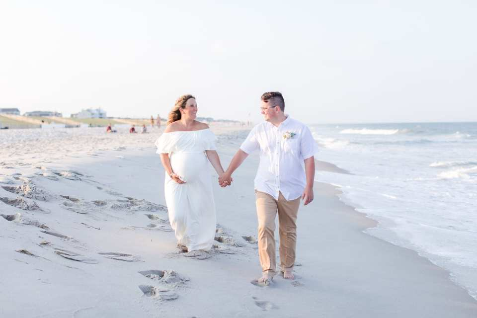 The bride and groom, she in an off the shoulder white gown, he in khakis and a short sleeve white button down shirt, walking on the beach down by the water