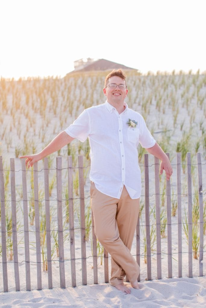 groom in casual khakis and white short sleeve button down shirt on the beach in Lavallette