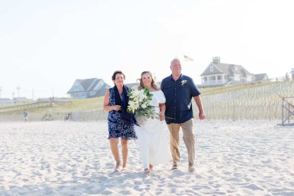The bride being walked on the beach to the ceremony by her mother and father