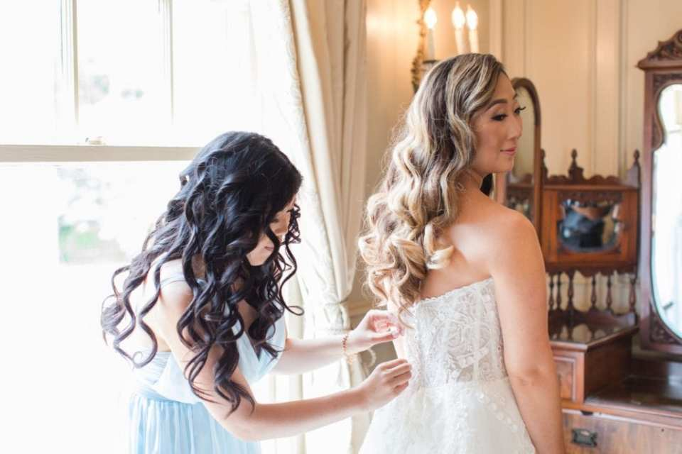 The bride being helped into her Maggie Sottero gown by one of her bridesmaids. Hair by The Glam Team