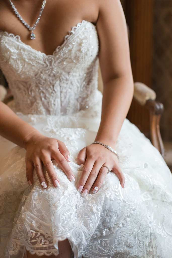 Portrait of the bride sitting down, face not in the picture, highlighting the detail on her Maggie Sottero gown