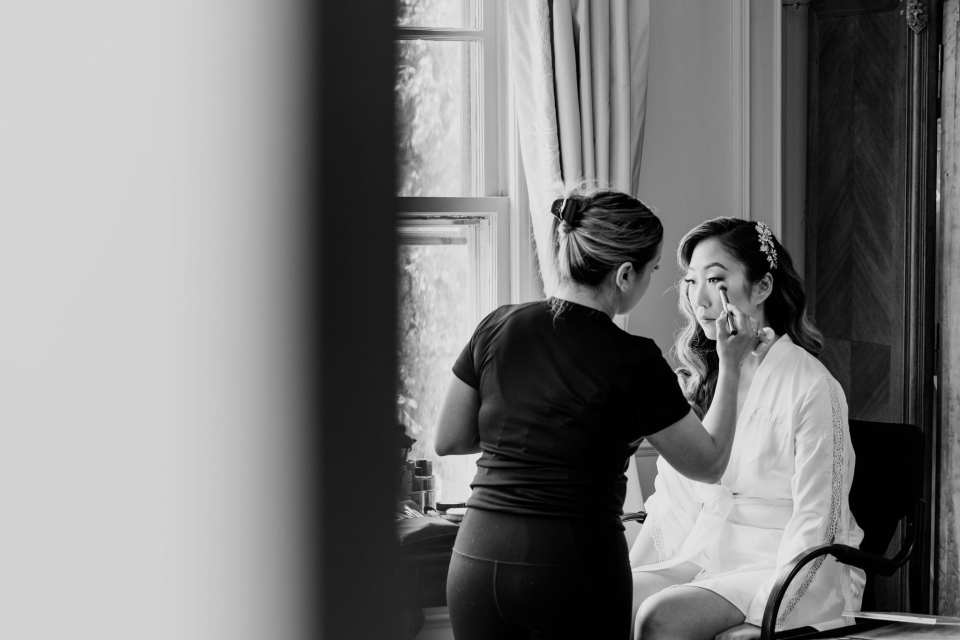 Black and white candid of the brides makeup being done by a member of the Glam Team