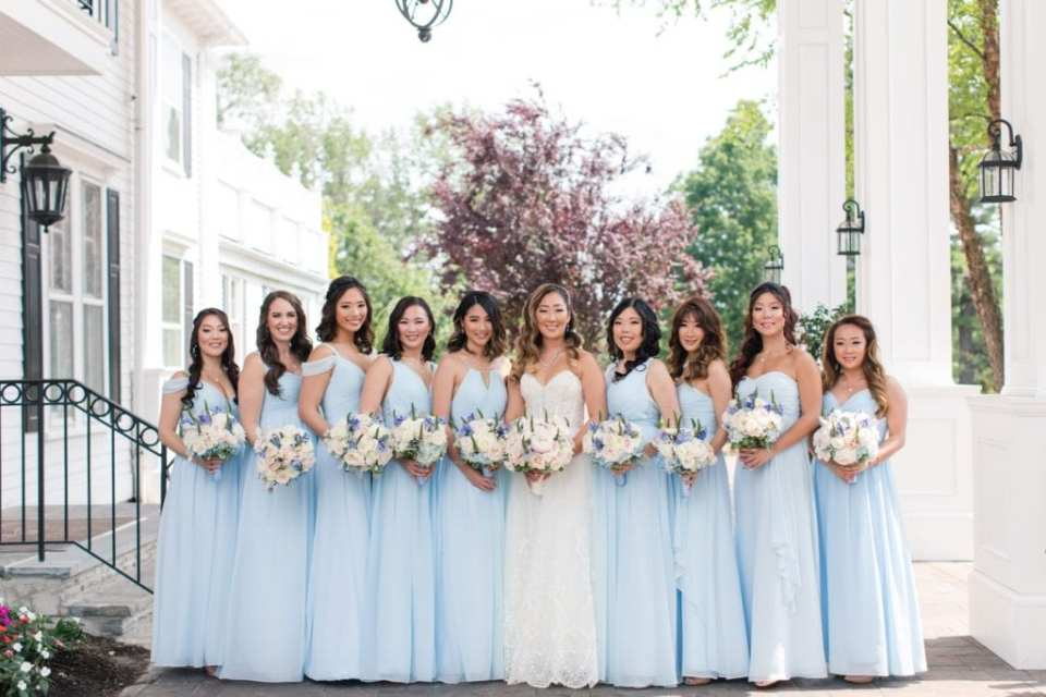 The bride and her bridesmaids in a formal picture, bridesmaids in pale blue gowns by Renzrags, bride in a gown by Maggie Sottero, with their bouquets of off white florals with blue floral and greenery accents by Crest Florists