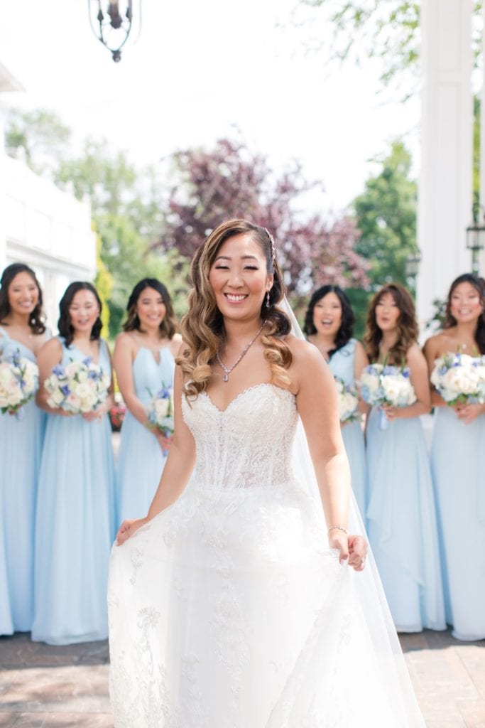 bride in her Maggie Sottero gown stands in front of her bridesmaids in their pale blue Renzrags gowns