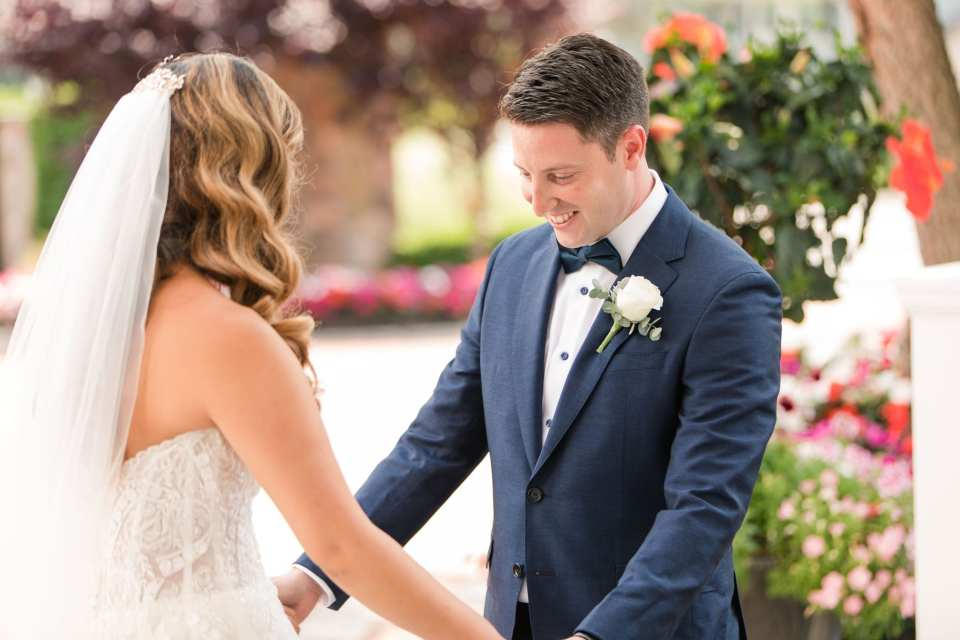 The groom holds his brides hands out as he smiles, checking out her gown during their first look