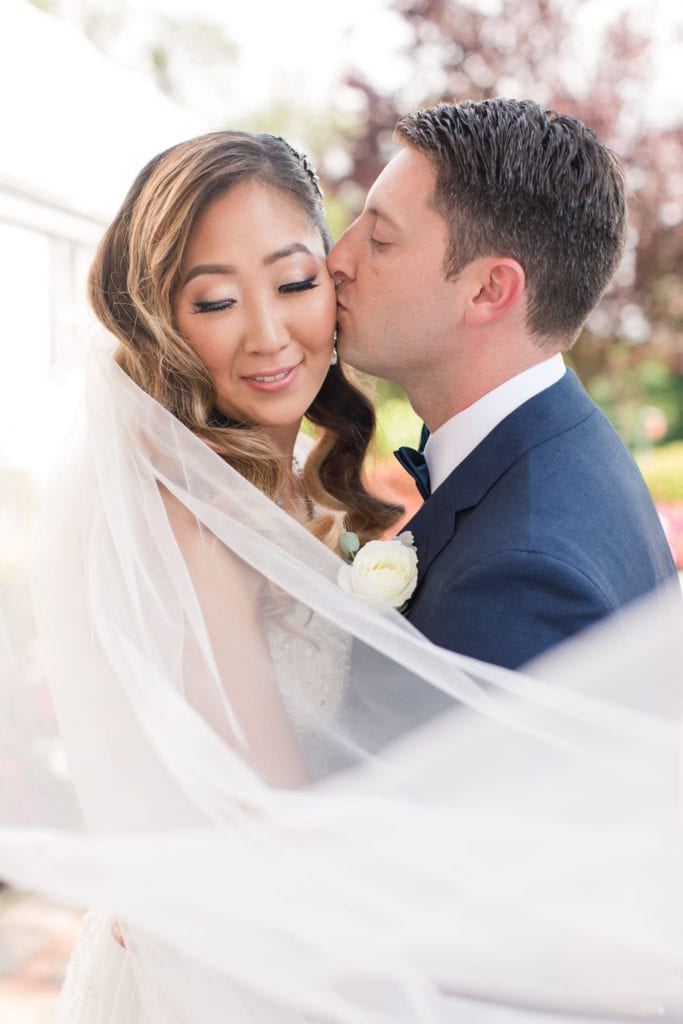 Shot from behind the veil as the groom kisses his brides cheek; she is looking down towards the camera