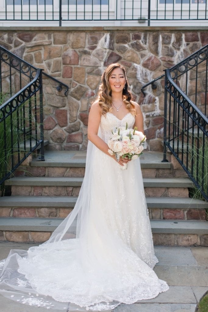 Formal portrait of the bride at base of stone steps at the Park Savoy Estate
