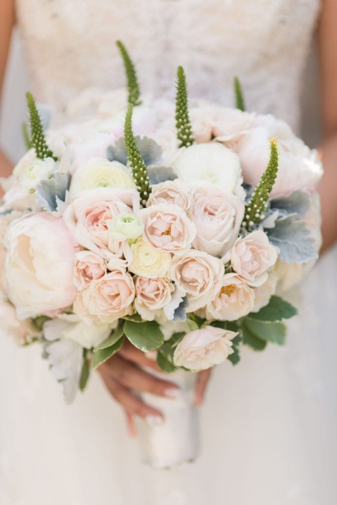 Bridal bouquet of various off white florals, with a few unique greens throughout by Crest Florals