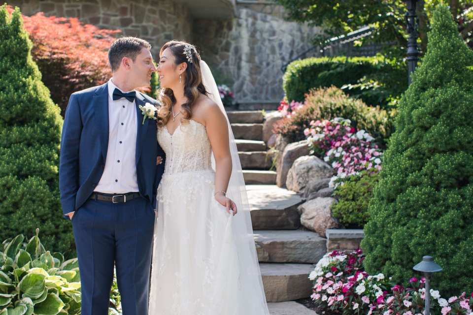 Bride and groom standing at the bottom of steps for their Park Savoy Estate wedding photos