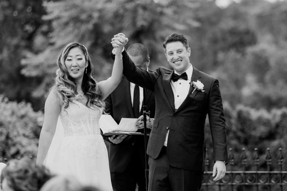 """Black and white photo of the bride and groom raising their arms after saying """"i do"""""""
