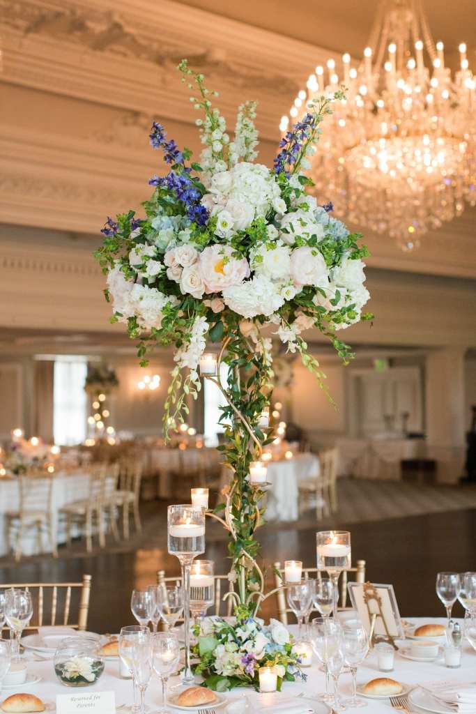 Full length photo of a tall floral arrangement of various white, pale blue and pale pink flowers sitting atop a gold candleabra with a twisting bottom by Crest Florist