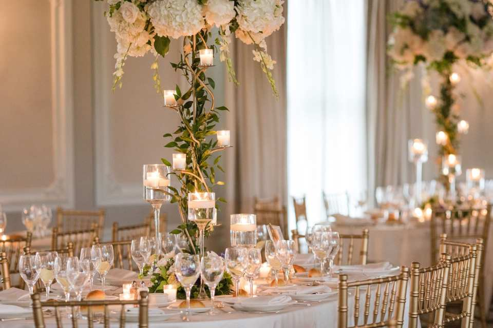 Close up of a reception table with white linens, a tall floral arrangement on a twisting stand, surrounded by voitives at various heights. There are gold chivari chairs at the table