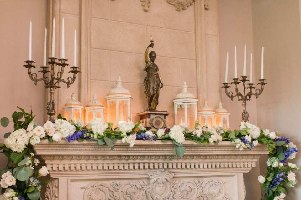 Wedding details shot of a fireplace mantel decorated by Crest Florals with white florals and greenery, with a touch of blue flowers scattered throughout. Cream colored candle lanterns, a gold candleabra, and a gold statue of a woman are in the background