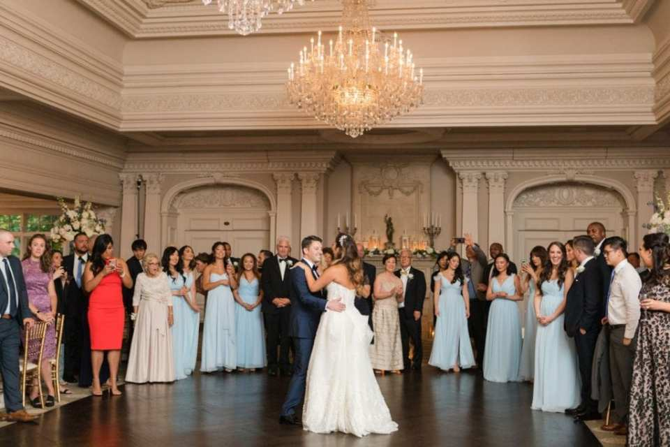 Wide angle photo of the bride and groom during their first dance as husband and wife, the guests and members of the wedding party surrounding them, watching